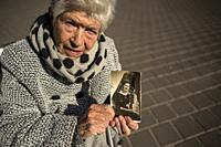 Old woman holding a photo of her youth, memories