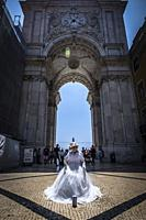 Famous arch at the Praca do Comercio, Lisbon, Portugal, with a street performer.