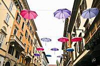 Monza, Brianza, Lombardy, Northern Italy. A downtown street with an artistic installation with open rain umbrellas suspended in the air.