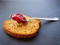 A spoon with raspberry jam on a slice of toast on a plate slate.