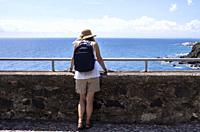 Woman in lookout, Aci Castello, Catania, Sicily, Italy.