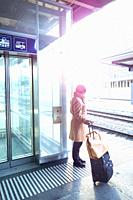 Woman With Luggage on Railroad Station with Sunlight in St Gallen, Switzerland.