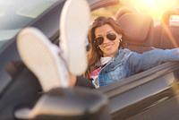 Happy young woman enjoying her convertible car.