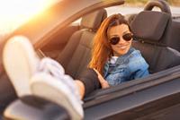 woman enjoying convertible car at sunset.