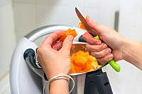 woman hands Preparing pumpkin puree in cook machine.