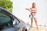Young woman washing car with hose. Car detailing.