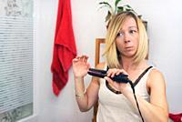 Beautiful natural blond girl using hair iron at home.