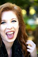 A laughing 25 year old redheaded woman looking at the camera in a garden setting.