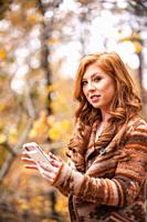 A 25 year old redheaded woman checking her cell phone in a forest setting.
