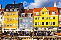 Alfresco canalside tables and chairs and brightly painted townhouses, Nyhavn, Copenhagen, Denmark, Scandinavia. 17th century waterfront canal and ente...