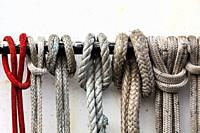 Ropes secured to a handrail on the cabin of a commercial fishing vessel.