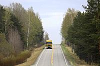 Salo, Finland - April 26, 2019: Road landscape on a day of spring with yellow and green Renault Trucks T semi trailer transporting load.