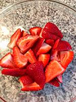 Sliced Strawberries in a glass bowl on a granite kitchen worktop.