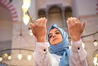 Muslim woman in headscarf and hijab prays with her hands up in air with mosque on background. Religion praying concept.