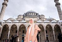 Beautiful Muslim woman in headscarf and fashionable modern trendy clothes poses at courtyard of Suleymaniye Mosque in Istanbul,Turkey. Modern Muslim w...