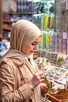 Beautiful Muslim woman in headscarf and fashionable modern clothes looks at spices sold in Egypt Bazaar in Eminonu,Istanbul,Turkey. Modern Muslim wome...