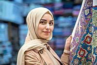 Beautiful Muslim woman in headscarf and fashionable modern clothes looks atrug or carpet sold in Egypt Bazaar,Istanbul,Turkey. Modern Muslim women lif...