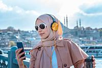 Beautiful Muslim woman in headscarf and fashionable modern trendy clothes with headphones,smartphone and sunglasses takes selfie with mosque view.