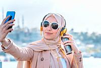 Beautiful Muslim woman in headscarf and fashionable modern trendy clothes with headphones,smartphone and sunglasses takes selfie.