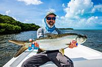 A fly fisherman with a small tarpon that caught with a fly rod on los roques - venezuela.