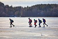 Long distance ice skaters on Lake Malaren and in foreground unmanned ice fishing hole, Sigtuna, Sweden, Scandinavia