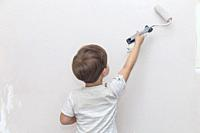 3 years cute little boy with paint roller in hand. Kids Helping House Chores concept.