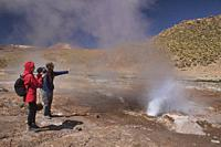 Watching a geyser erupt along the Rio Blanco, El Tatio, San Pedro de Atacama, Chile.
