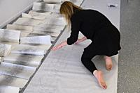 A woman artist aged 50 to 55 years old creates performance art that incorporates drawing, text, and walking.