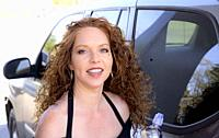 A beautiful redheaded woman pumping gasoline for her car.