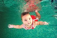 A little girl in red swimmiing suit learns to swim underwater in the pool. Baby swimming underwater in the pool. Healthy family lifestyle and children...