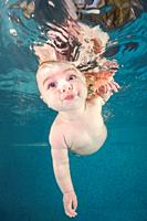 Little baby boy learning to swim underwater in a swimming pool. Healthy family lifestyle and children water sports activity. Child development, diseas...