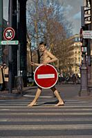 young naked man with prohibition sign walking at street, in Paris, France.