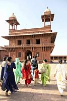 local family in a Red sandstone buildings of the Fatehpur Sikri complex built by the great Mughal emperor Akbar beginning in 1570 in Fatehpur Sikri, I...