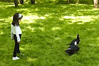 Adorable four years old cute little girl watches ducks in a green garden. Nature and kid concept.