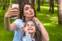 Young mom and little girl takes selfie together. Happy mother and daughter moments with love and natural emotion. Photo of young mother and her daught...