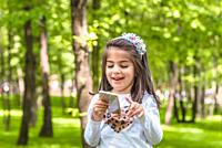 Adorable four years old cute little girl in casual clothes holds and texts mobile phone while smiling at outdoor in park.