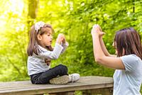 Young mom shows her little girl how to make heart shape on bench in forest. Happy mother and daughter moments with love and natural emotion.
