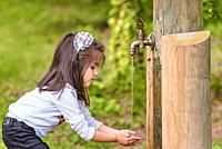 Adorable four years old cute little girl drinks water from a wooden tap in forest at a sunny day.