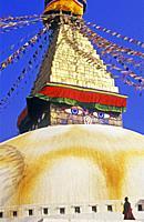 Buddhist monk walking around Bodnath stupa, Boudhanath, Katmandu, Nepal, Asia.