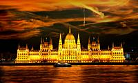 Facade of illuminated Budapest Parliament under cloudy sky, Hungary.