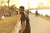 African man looking backwards over shoulder, running next to river Main, in Frankfurt, Germany.