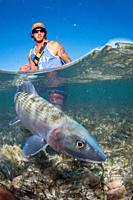 Over/under type shot SPLIT off man hold a BIG BONEFISH underwater saltwater fly fishing los roques venezuela.