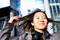 young sanguine Asian woman playing with hairs, in business district in Paris, France.