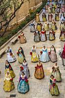 Falleras. Women in traditional dress. Parade to the Plaza de la Virgin in order to make an offering of flowers to Our Lady of the Forsaken, the Patron...