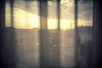 View across a window with a curtain at the dawn of the city. Bucharest, Romania, Europe