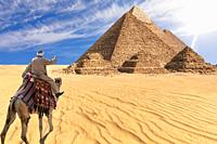 A bedouin of Giza desert in front of the Great Pyramids, Egypt.