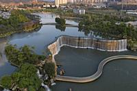 Aerial 360 degree view of the Kunming Waterfall Park at sunset, one of the largest manamde waterfalls in the world.