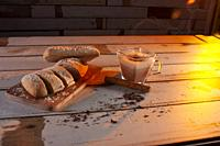 Cup with hot chocolate steaming accompanied by a piece of cinnamon and a baguette finely cut into slices ready for breakfast studio photography with c...