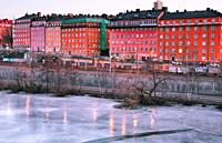 Dawn light on the frozen ice of Karlberg Lake (Karlbergssjon) with the colourful facades of the Atlas district houses, Norrmalm, Stockholm, Sweden, Sc...