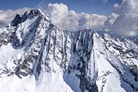 aerial, from a small plane, of snow, ice and rocks of Disgrazia peak north side, shot in bright springtime light from Valmalenco, Sondrio, Italy.